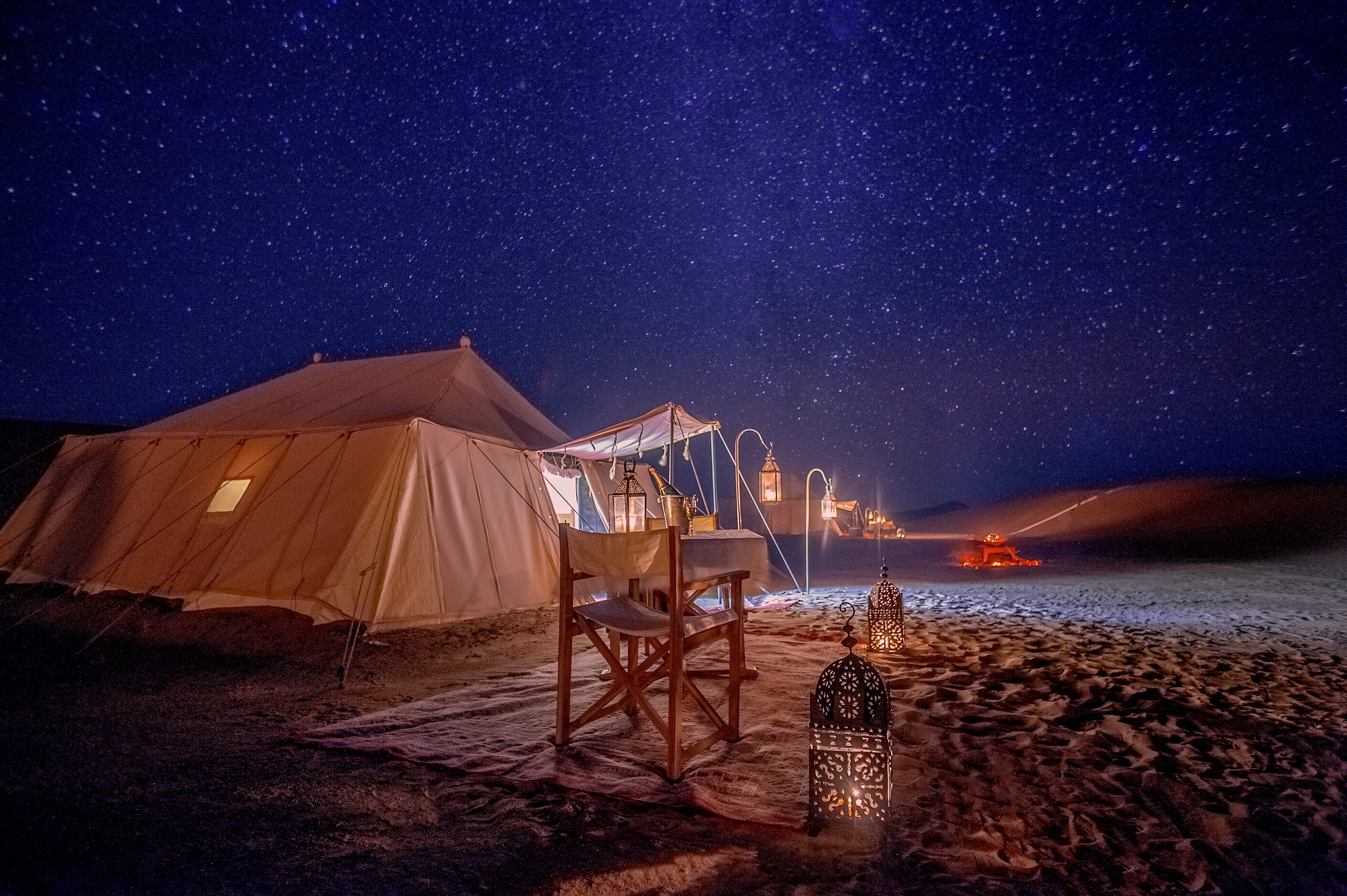 Glamping tents under starry night sky somewhere in the wilderness.